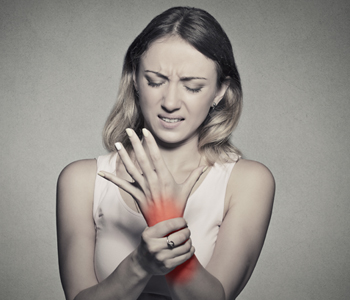 Young woman holding her painful wrist